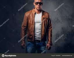 handsome blond muscular man in sunglasses dressed in a white t shirt and brown leather jacket photo by fxquadro