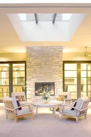 double sided fireplace indoor outdoor patio contemporary with armchairs concrete exterior skylight image by nest architectural