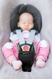 newborn baby girl sitting in a car seat stock photo
