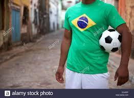 Il brasiliano street football player in piedi in bandiera Brasile t-shirt  tenendo palla calcio in un vecchio villaggio rustico Foto stock - Alamy