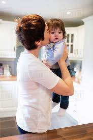 cute mother kissing her baby in the kitchen