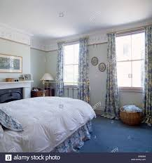 Blue carpet and floral patterned curtains in traditional bedroom with white  duvet on brass bed