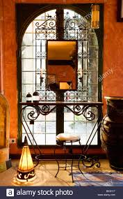 metal hall table. Mirror Above Metal Console Table In Front Of Moroccan-style Arched Window Spanish Hall With Lighted Lamp On Floor