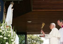 Pope raising a chalice to a statue of Mary