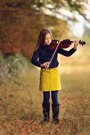 young girl playing violin in yellow skirt with navy jumper and tights surrounded by autumn colours