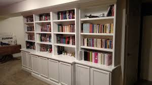 custom painted built in bookcase with adjule shelves and enclosed cabinets