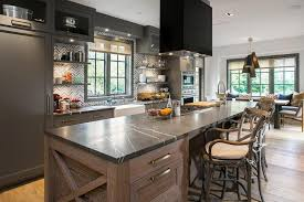 long kitchen island with cooktop and hood
