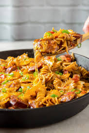 a skillet of cheesy smoked sausage pasta with a wooden spoon lifting a serving out of