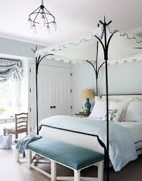 lovely blue gray bedroom design with blue gray walls paint color black iron oscar de la renta canopy bed white hickory bench upholstered in blue velvet blue grey paint colors view