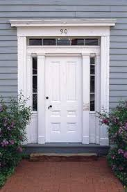 a white door with transom and sidelights is centered in a grey