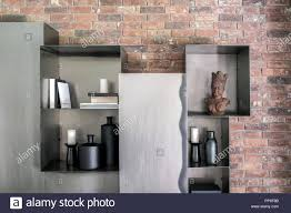 glossy metal lockers with shelves on the brick wall background in the modern interior on the shelves there are books black vases and candlesticks c