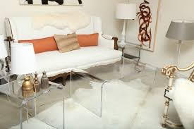 very small spaces living room decoration with square clear acrylic coffee table and white leather sofa with wooden base plus glass table lamp with shelves