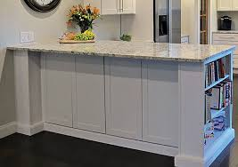 kitchen peninsula in white cabinets with bookcase end decorative door panels on back and ogee