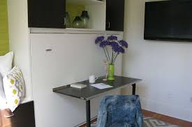 micro space is possible due to murphy bed unit with drop down table mounted on the
