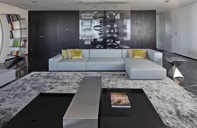 light grey l shaped leather floor couch and huge area rug in minimalist modern living room