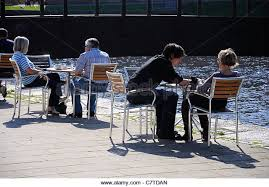 people sitting at cafe table. people sitting at outdoor cafe tables. exeter quayside, devon, uk. - stock table o