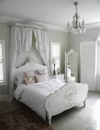 white and grey shabby chic bedroom with a crystal chandelier
