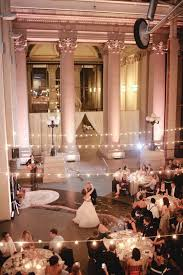 a couple dances under strings of lights during a wedding in macdermott grand hall