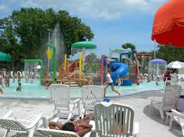 people play in a shallow pool area with slides and other equipment while others lounge in