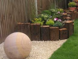 garden design using sleepers. garden bed retaining created with vertical railway sleepers design using