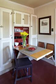 rectangular beige wooden fold down dining table with red shelves plus folding chair built in kitchen cabinet