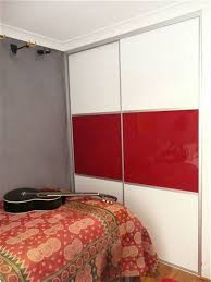 a bedroom with a bed and guitar the sliding wardrobe doors have three panels