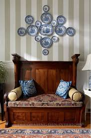 Wooden bench with pilows and blue and white china plates on wall