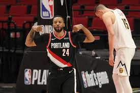 Portland trail blazers guard damian lillard, left, hits a shot over denver nuggets guard facundo campazzo, center, and center nikola jokic, right, during the first half of game 4 of an nba. Oaa Ggv 6cifwm