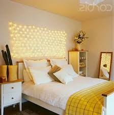 bedroom string lights on wall above bed