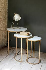 round nest of 3 marble side tables on white wooden floor and dark green background table