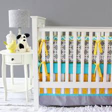 light blue and gray white bedding plus orange white bedding placed on the white wooden crib