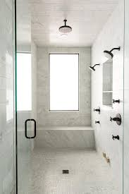and walls clad in carrera marble tiles fitted with a carrera marble slab shower bench placed under a window alongside a mosaic marble shower floor