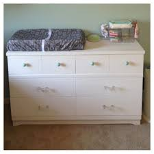 small white wooden changing table dresser for nursery having hutch and drawers plus round knobs on beige carpet flooring furniture cabinet hardware pulls