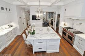 another look of the kitchen featuring the room s hardwood flooring white walls countertops and