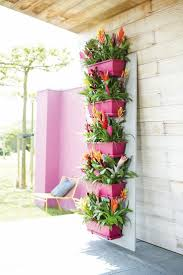a nice way to brighten up your balcony - brightly painted flower pots  placed vertically on