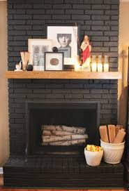 brick fireplace painted a dark gray almost black with wood mantel and home decor by cavender