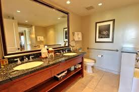 extra large bathroom mirror featuring wooden vanity with granite countertop