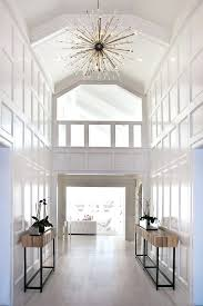 large hallway chandeliers stunning two story foyer white moulding on walls wood side tables gladiator spiked