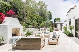 alyssa rosenheck gray teak patio furniture with white stucco fireplace