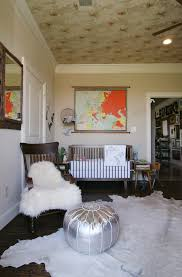 gorgeous moroccan pouf in nursery eclectic with hanging rug next to cowhide rug alongside dark hardwood flooring and vaulted ceilings crown moulding