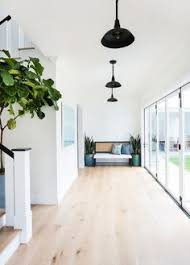 foyer the foyer has a very airy and open feel thanks to the walls painted in a warm white folding patio doors and the wide whitewashed plank hardwood