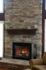after makeover tall floor to ceiling fireplace with black insert with glass cover and raised hearth
