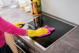 person cleaning glass stove top with microfiber cloth