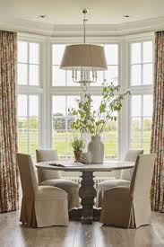a beautiful round dining table and chairs with covers in front of bay window looking out in the fields the traditional english home by sims hilditch the