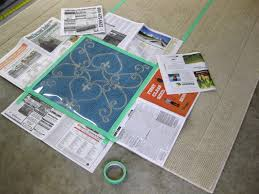tape down the stencil and make sure to surround it with newspaper to prevent any paint