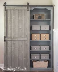 hidden storage behind a diy sliding barn door on bookcases