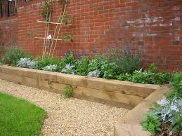 garden design with sleepers. raised garden along a brick wall adds color design with sleepers u