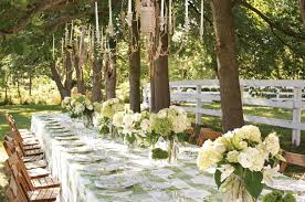 outdoor party in park with long table decor flowers on it and wooden chair under the