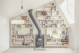above the asymmetrical interior wall bedecked in bookshelves sink and freestanding wood stove all that s missing is a messy potting table