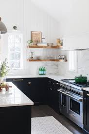 black kitchens are just as classic but more a bolder choice i love this with those light countertops and the verticle shiplap